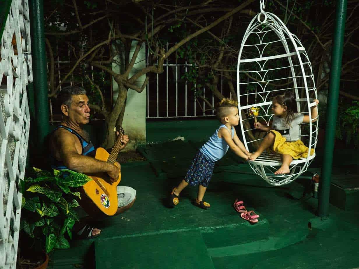 אישה מנגנת בגיטרה בזמן שילדים משחקים ברקע