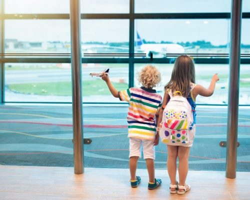 Kids at airport. Children look at airplane. Traveling and flying with child. Family at departure gate. Vacation and travel with young kid. Boy and girl before flight in terminal. Kids fly a plane.